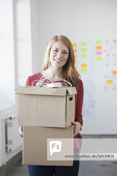 Junge Frau im Büro mit Pappkartons