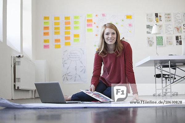 Junge Frau im Büro sitzt auf dem Boden und arbeitet sich durch Papiere.