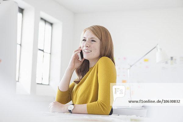 Junge Frau im Büro arbeitet am Schreibtisch  mit Smartphone