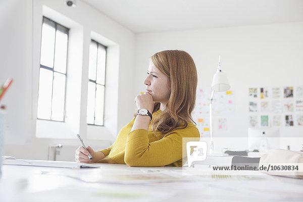 Junge Frau im Büro arbeitet am Schreibtisch