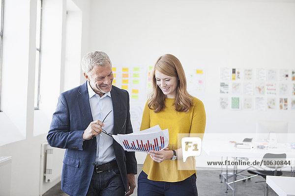 Kaufmann und Mitarbeiter im Büro studiert Infografik