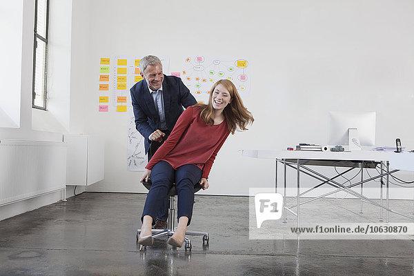 Geschäftsmann schiebt junge Frau auf Stuhl durchs Büro