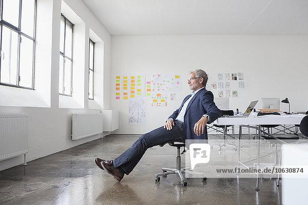 Ein reifer Geschäftsmann sitzt im Büro und schaut zum Fenster.