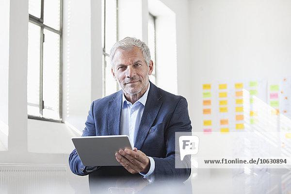 Porträt eines Geschäftsmannes im Büro mit digitalem Tablett