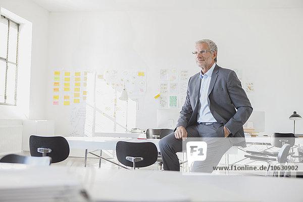 Geschäftsmann im Büro auf dem Schreibtisch sitzend