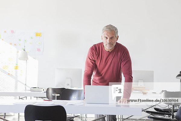 Portrait eines selbstbewussten Geschäftsmannes mit Laptop im Büro