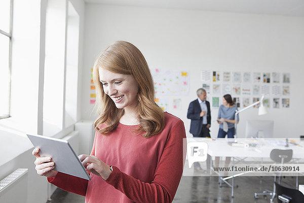 Lächelnde junge Frau mit digitalem Tablett im Büro