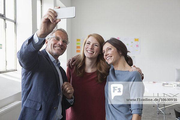 Smiling businessman taking a selfie with two women in office