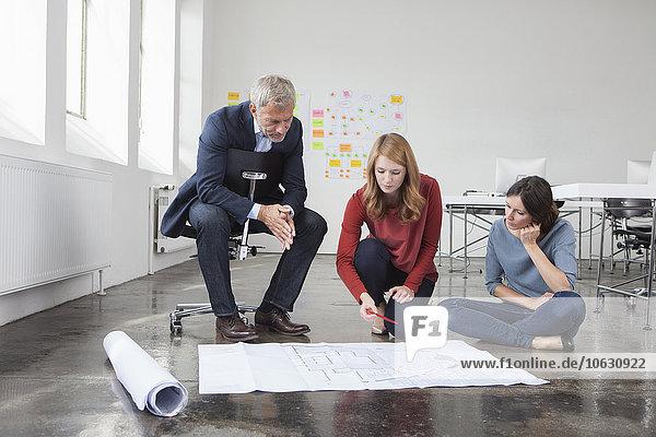 Geschäftsmann und zwei Frauen im Büro beim Betrachten des Bauplans