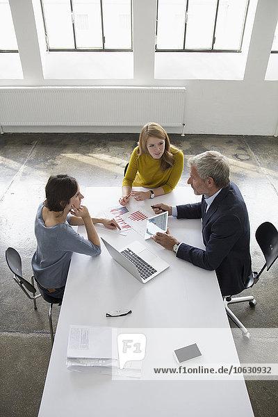 Geschäftsmann und zwei Frauen im Konferenzraum bei einer Besprechung