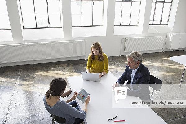Geschäftsmann und zwei Frauen im Konferenzraum mit tragbaren Geräten