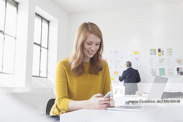 Lächelnde junge Frau im Büro am Schreibtisch mit Laptop und Handy