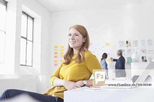 Lächelnde junge Frau im Büro am Schreibtisch