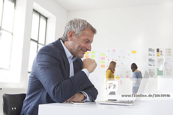 Lächelnder Geschäftsmann im Büro am Schreibtisch mit Blick auf den Laptop