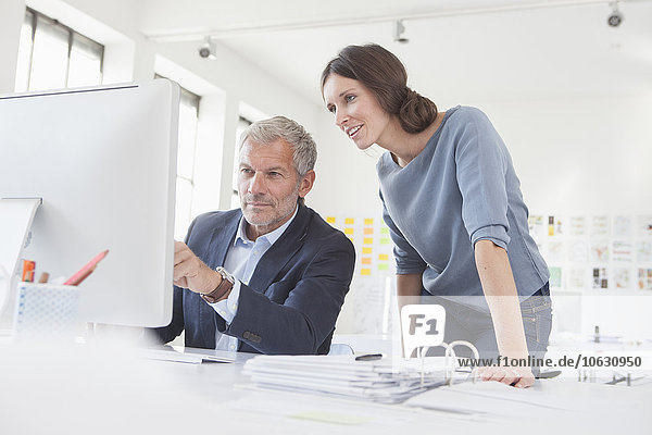 Geschäftsmann und Frau im Büro bei der gemeinsamen Arbeit am Computer