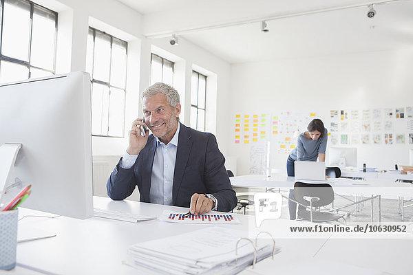 Lächelnder Geschäftsmann im Büro am Schreibtisch auf dem Handy