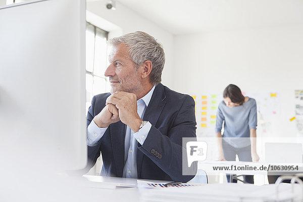 Lächelnder Geschäftsmann im Büro am Schreibtisch