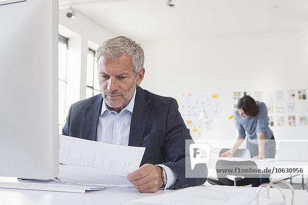 Geschäftsmann im Büro am Schreibtisch mit Blick auf Papier