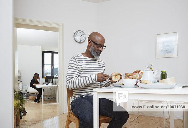 Mann beim späten Frühstück in seinem Home-Office