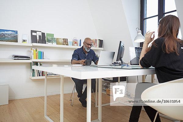 Zwei Personen arbeiten am Schreibtisch in einem Büro.