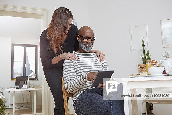 Paar mit digitalem Tablett in der Küche