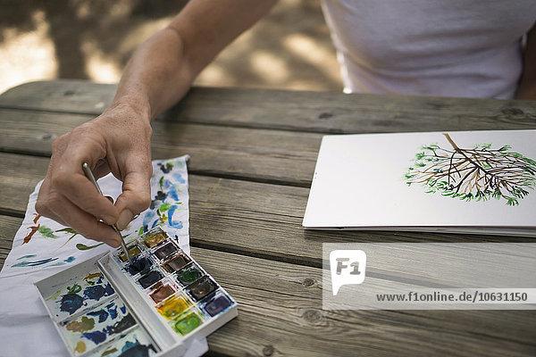 Frau malt Baum auf Holztisch im Freien