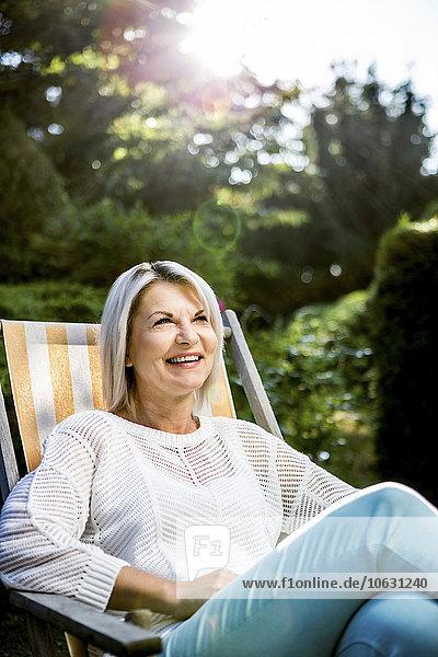 Reife Frau entspannt im Liegestuhl im Garten