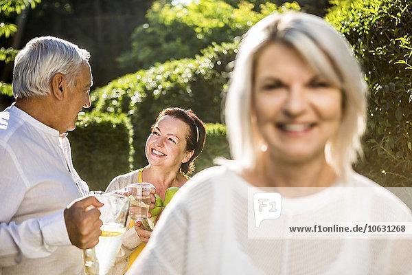 Mann und Frau im Garten mit lächelnder Frau im Vordergrund