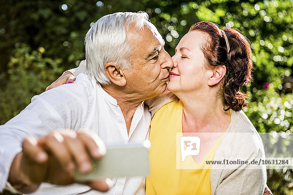 Elderly couple kissing and taking selfie outdoors