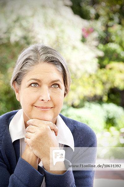Porträt einer lächelnden Frau  die im Garten sitzt. Porträt einer lächelnden Frau, die im Garten sitzt.
