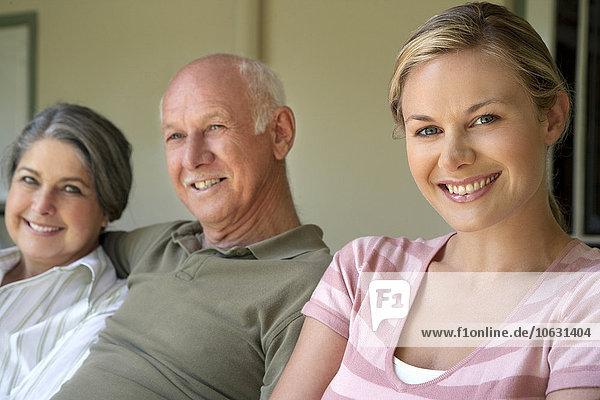 Porträt einer lächelnden Frau mit ihren Eltern im Hintergrund