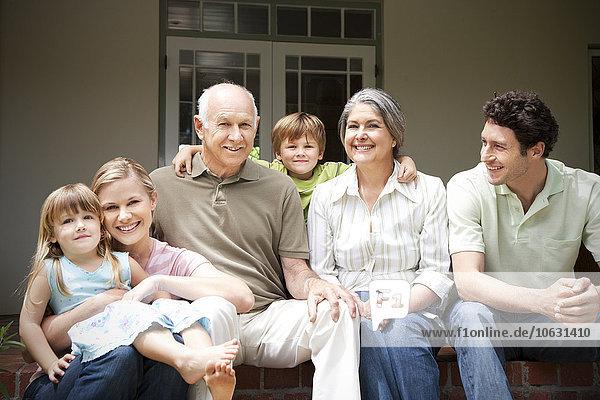 Gruppenbild von drei Generationen Familie auf der Terrasse sitzend Gruppenbild von drei Generationen Familie auf der Terrasse sitzend