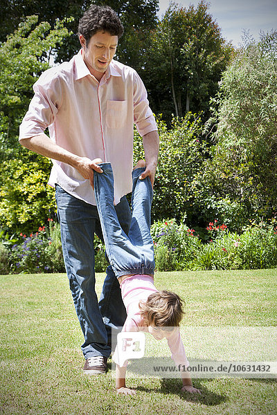Mann spielt mit seiner kleinen Tochter im Garten Mann spielt mit seiner kleinen Tochter im Garten