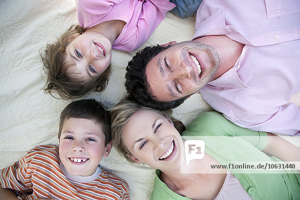 Gruppenbild einer glücklichen Familie auf einer Decke liegend