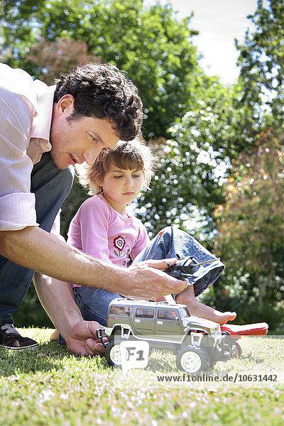Mann und seine kleine Tochter mit Spielzeugauto im Garten