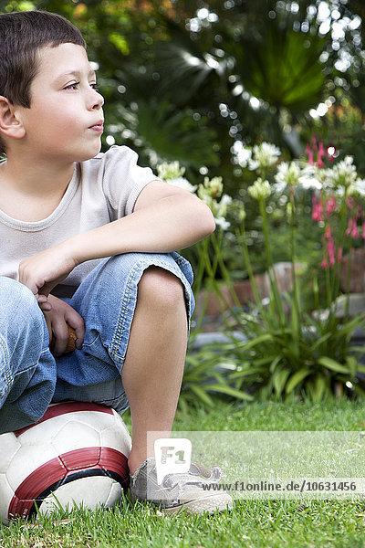 Kleiner Junge sitzt auf einem Fußball im Garten. Kleiner Junge sitzt auf einem Fußball im Garten.