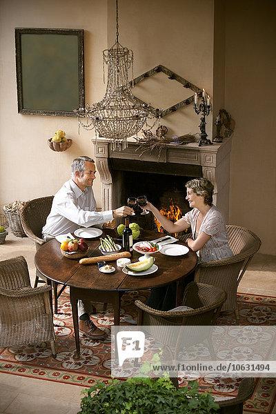 Ein reifes Paar sitzt am gedeckten Tisch und toastet mit Rotwein vor offenem Feuer. Ein reifes Paar sitzt am gedeckten Tisch und toastet mit Rotwein vor offenem Feuer.