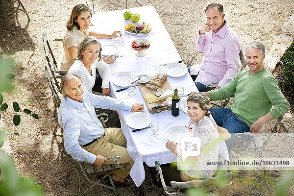 Sechs Freunde sitzen am gedeckten Tisch im Garten und schauen zur Kamera. Sechs Freunde sitzen am gedeckten Tisch im Garten und schauen zur Kamera.