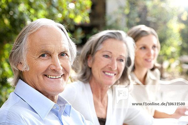 Porträt eines lächelnden älteren Mannes und zweier Frauen im Hintergrund  die im Garten sitzen.