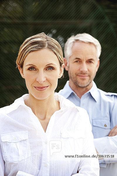 Porträt einer lächelnden jungen Frau mit ihrem Mann im Hintergrund