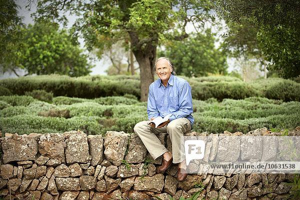 Spanien  Mallorca  Porträt eines entspannten älteren Mannes mit einem Buch an der Wand im Garten Spanien, Mallorca, Porträt eines entspannten älteren Mannes mit einem Buch an der Wand im Garten