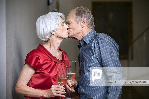 Seniorenpaar küsst und klirrt an den Gläsern