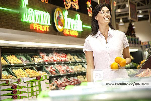 Porträt eines lächelnden Kunden mit drei Orangen im Supermarkt