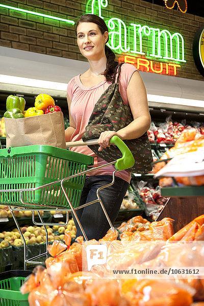 Porträt eines lächelnden Kunden mit Einkaufswagen beim Gemüsekauf im Supermarkt