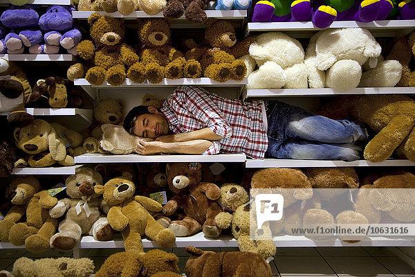 Mann schläft auf einem Regal zwischen Plüschtieren im Supermarkt Mann schläft auf einem Regal zwischen Plüschtieren im Supermarkt