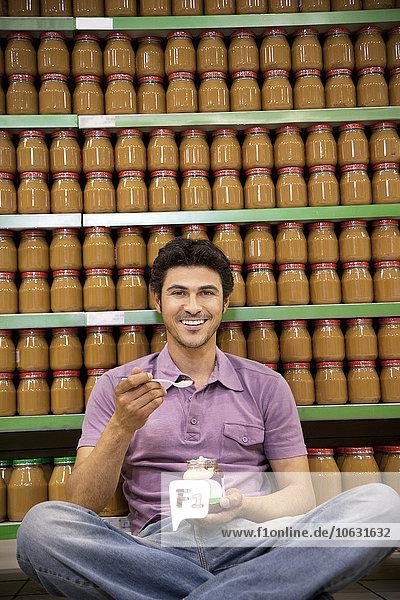 Lächelnder Mann sitzt auf dem Boden eines Supermarktes und probiert ein Glas Schokoladenaufstrich. Lächelnder Mann sitzt auf dem Boden eines Supermarktes und probiert ein Glas Schokoladenaufstrich.