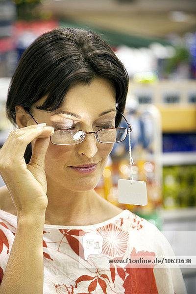 Frau in einem Laden  die eine Brille anprobiert. Frau in einem Laden, die eine Brille anprobiert.