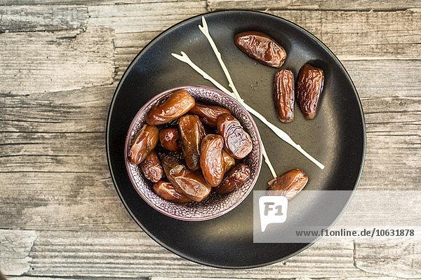 Schale mit Datteln  Spieße und Teller auf Holz