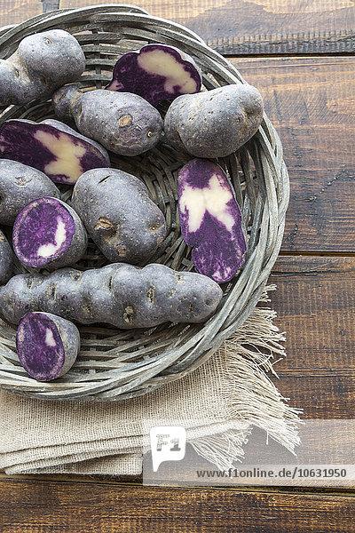 Geschnittene und ganze violette Kartoffeln in einem Weidenkorb
