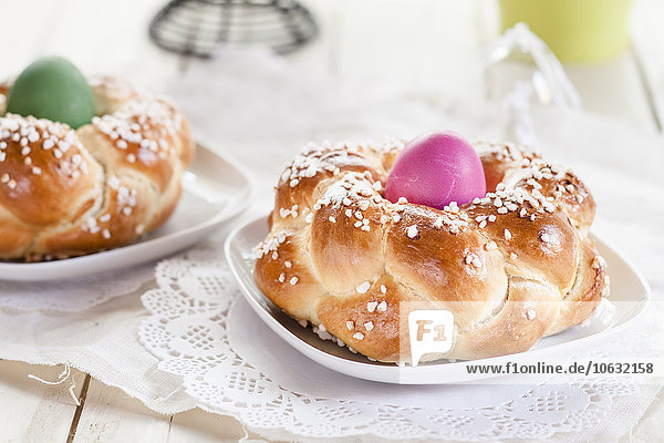 Geflochtenes Osterbrot mit grünen und rosa Eiern
